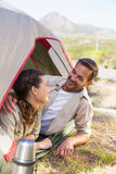 Outdoorsy couple smiling at each other inside their tent Stock Images