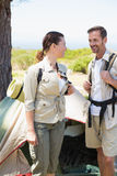 Outdoorsy couple smiling at each other outside their tent Stock Photos