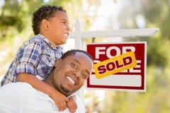 Outdoorsy Mischrasse-Vater und Sohn vor Verkaufs-Real Estate-Zeichen Stockbild
