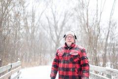 Outdoorsymens die in plaid over brug tijdens sneeuwval lopen Royalty-vrije Stock Afbeeldingen