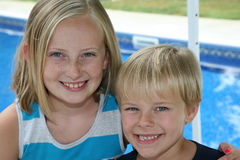 Outdor Bild eines jungen Jungen und des Mädchens durch das swimmi Lizenzfreie Stockfotografie