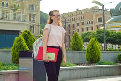 Outdor portrait of female student 16, 17 years old. Girl in glasses, with backpack, textbooks. City background. Outdor portrait of female student 16, 17 years stock photos
