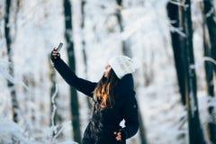 Outdors de la muchacha en el bosque que toma la foto con el teléfono (selfie) Foto de archivo libre de regalías