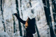Outdors de la muchacha en el bosque que toma la foto con el teléfono (selfie) Foto de archivo