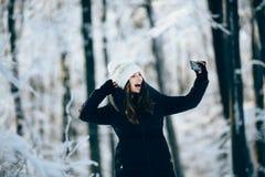 Outdors de la muchacha en el bosque que toma la foto con el teléfono (selfie) Fotos de archivo