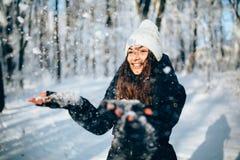 Outdors de sopro da neve da menina nos flocos de neve e no sorriso da captura da floresta Imagens de Stock