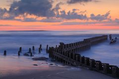 Outer Banks NC Calm Sea. Calm ocean waves at the erosion control barrier in the Atlantic Ocean on Cape Hatteras National Seashore at sunrise in the Outer Banks Stock Image