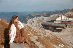 Outfit of casual woman. Brunette sitting on bench enjoying nature above mountains view landscape. Travel Lifestyle adventure. Vacations outdoor. Girl wearing stock image