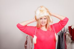 Attractive woman wearing furry winter hat. Outfit for cold days ideas, fashion and clothing concept. Attractive smiling blonde woman in wardrobe, picking clothes Royalty Free Stock Photo