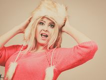 Attractive woman wearing furry winter hat. Outfit for cold days ideas, fashion and clothing concept. Attractive smiling blonde woman wearing furry winter hat Stock Photos