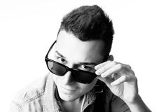 Outfit of a fashion guy with jacket and black sunglasses on white background studio black and white Stock Image
