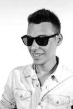 Outfit of a fashion guy with jacket and black sunglasses on white background studio black and white Royalty Free Stock Photo