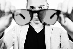 Outfit of a fashion guy with jacket and black sunglasses on white background studio black and white Stock Photography