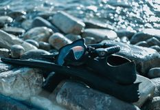 Outfit of freediver. Outfit of freediver on pebble coast near the sea, flippers and mask with snorkel Royalty Free Stock Photography