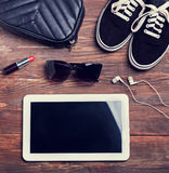 Outfit for modern young girl, top view. Toned photo. Outfit for modern young girl on wooden background, top view. Tablet, gumshoes, lipstick, earphones and bag Stock Images