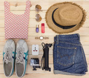 Outfit of traveler, student, teenager, young woman. Overhead of essentials for modern young person. Different objects on wooden ba Royalty Free Stock Photography