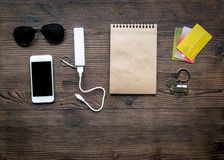 Outfit of traveller with sunglasses and mobile on wooden background top view. Outfit of traveller with sunglasses and mobile on wooden table background top view Stock Images