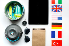 Outfit for trip with flags and tablet on white background top view Stock Photo