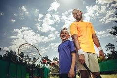 Outgoing boy and male playing tennis royalty free stock photo