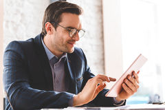 Outgoing businessman watching at digital device screen Stock Photo