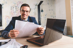 Outgoing businessman watching at paper in office Royalty Free Stock Photo