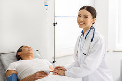 Outgoing doctor caring about sick male Royalty Free Stock Image