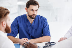 Outgoing doctor situating with colleagues during meeting Stock Image