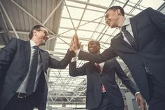 Outgoing employers giving high fives. Low angle happy businessmen expressing unity of company while holding hands together. Achievement during labor concept Royalty Free Stock Photos