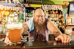 Outgoing fat male bartender giving beer Stock Photography