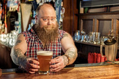 Outgoing fat man putting ale on table Stock Photo
