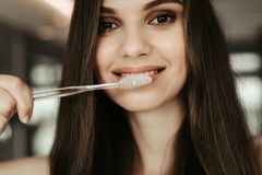 Outgoing female cleaning white teeth in room stock photography