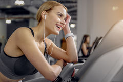 Outgoing female listening music in fitness center Royalty Free Stock Photography
