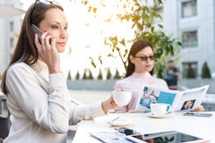 Outgoing female speaking by phone in cafe Stock Images