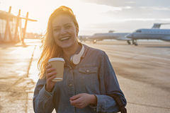 Outgoing female tasting beverage outdoor in airport Stock Photo