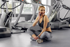 Outgoing female telling at cellphone in gym Royalty Free Stock Image