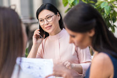 Outgoing female telling by mobile in cafe Stock Images