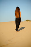 The outgoing girl. A girl in a black dress that goes in the sand Stock Images