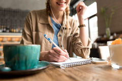 Outgoing girl making notes in scribbling-diary Royalty Free Stock Images