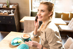 Outgoing girl telling at mobile in cafe Royalty Free Stock Image