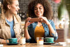 Outgoing girls making conversation at table Royalty Free Stock Image