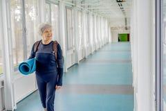 Outgoing grandmother walking along corridor after yoga Stock Photos