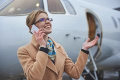 Outgoing lady speaking by mobile near plane. Glad girl enjoying snow while talking by phone. She standing opposite aircraft on street. Communication and Stock Photos