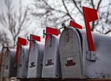Outgoing Mail. Row of galvanized or silver mailboxes with the red flags up signaling to the mailman there is outgoing mail.  This is typical of a rural scene in royalty free stock photos