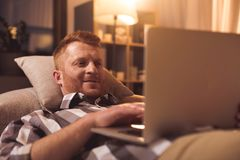 Outgoing male resting with notebook computer. Portrait of cheerful bearded man typing in laptop while lying on sofa in room. Relax concept Stock Image