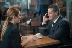 Outgoing male talking by phone. E view cheerful businessman speaking by mobile while drinking cup of coffee with happy wife. The sitting at table in cafe Royalty Free Stock Images