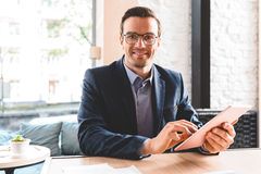 Outgoing male typing at electronic tablet Royalty Free Stock Photo