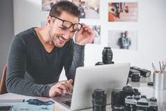 Outgoing male working with laptop in office. Portrait of cheerful young bearded photographer typing in digital device while locating at table in apartment Stock Photos