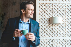 Outgoing man drinking mug of beverage Stock Photo