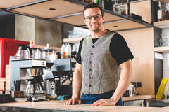Outgoing man standing at counter in cafe Royalty Free Stock Image