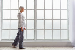 Outgoing old woman moving in room of clinic Royalty Free Stock Images
